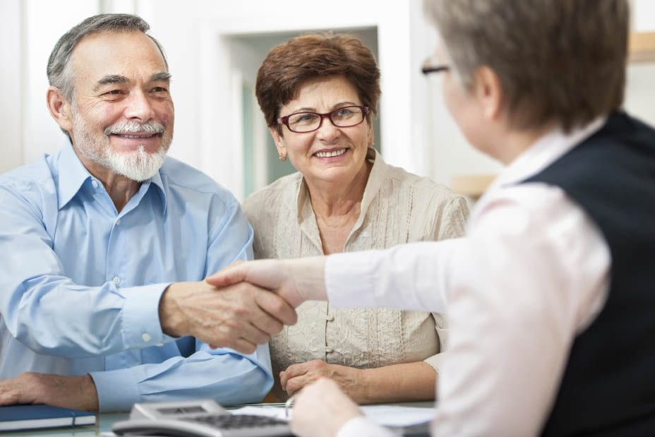 elderly couple shaking hands with worker